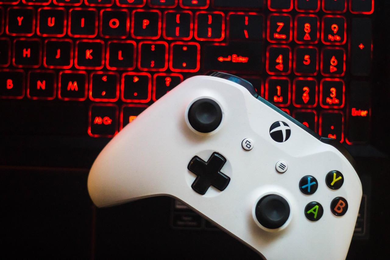controle de um console xbox com um teclado ao fundo