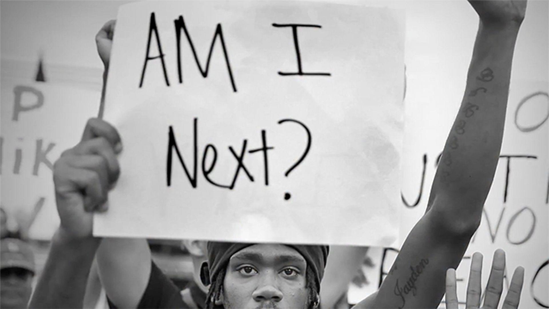 """Cena de a 13ª emenda, rapaz negro segurando cartaz """"Eu sou o próximo?"""" em protesto."""