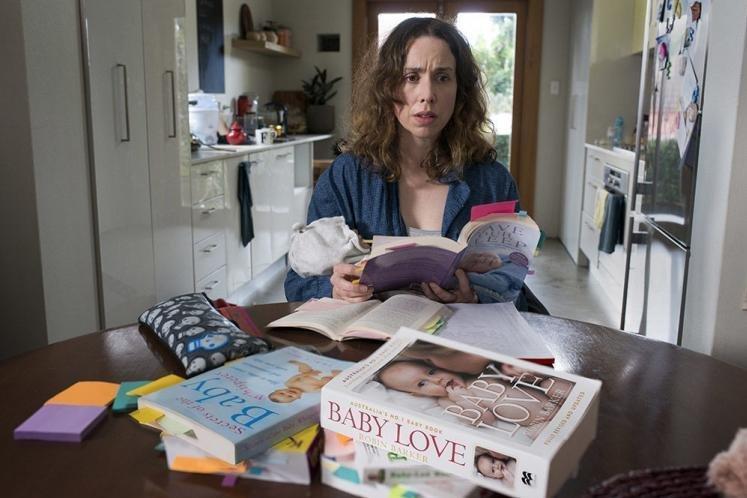 Alison Bell como audrey em Turma do Peito, rodeada de livros e bagunça